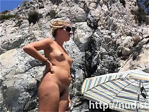 Spy cam shot of a sizzling nudist babe tanning on the beach